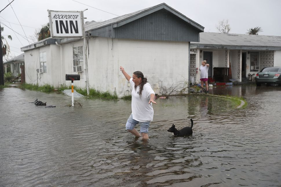 Valerie Brown walks through a flooded area after leaving her apartment in Rockport.