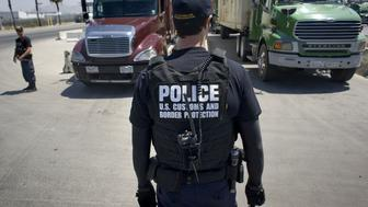 A U.S. Customs and Border Protection (CBP) officer stands in front of a line of trucks that will undergo a secondary inspection at the Otay Mesa Cargo Port of Entry in San Diego, California, U.S., on May 23, 2017. The skirmish among House Ways and Means Committee Republicans over a border tax provision resurfaced during a May 24 hearing where Treasury Secretary Steven Mnuchin was testifying on the president's proposed fiscal year 2018 budget. Photographer: David Maung/Bloomberg via Getty Images