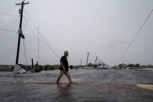 A man walks through floods waters after surveying his property, which was hit by Hurricane Harvey in...