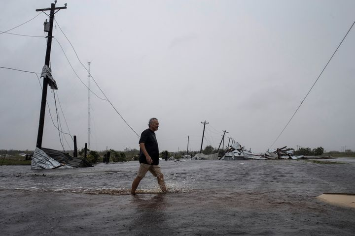 A man walks through floods waters after surveying his property, which was hit by Hurricane Harvey in Rockport, Texas.