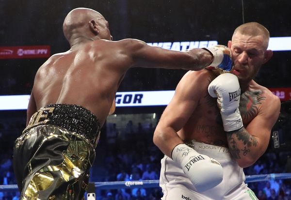 LAS VEGAS, NV - AUGUST 26:  (L-R) Floyd Mayweather Jr. throws a punch at Conor McGregor during their super welterweight boxin