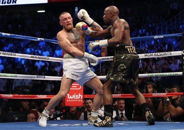 LAS VEGAS, NV - AUGUST 26:  (R-L) Floyd Mayweather Jr. throws a punch at Conor McGregor during their super welterweight boxin