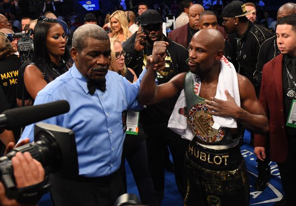 LAS VEGAS, NV - AUGUST 26:  Referee Robert Byrd raises the hand of Floyd Mayweather Jr. after his TKO of Conor McGregor in th