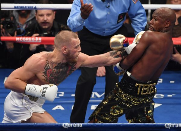 LAS VEGAS, NV - AUGUST 26:  (L-R) Conor McGregor throws a punch at Floyd Mayweather Jr. during their super welterweight boxin