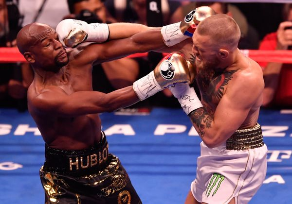 LAS VEGAS, NV - AUGUST 26:  (R-L) Conor McGregor throws a punch at Floyd Mayweather Jr. during their super welterweight boxin