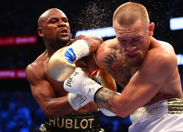 Floyd Mayweather Jr. lands a punch against Conor McGregor during their boxing match at the T-Mobile Arena...