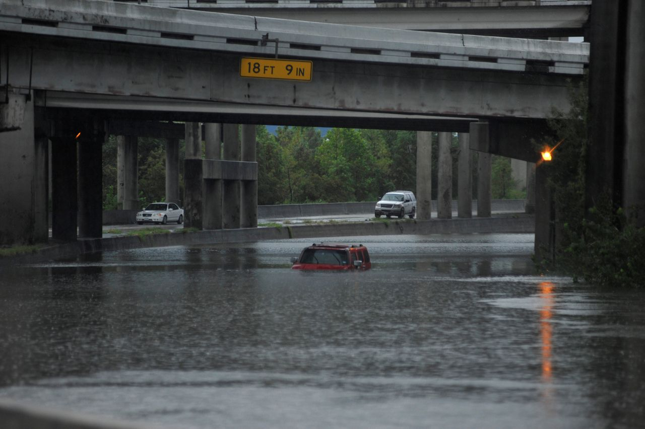 Floodwaters nearly cover an abandoned Hummer along Interstate 610 in Houston on Sunday.