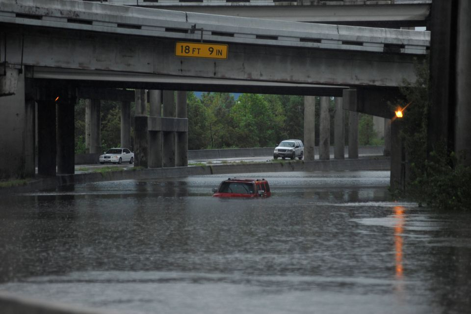 Floodwaters nearly cover an abandoned Hummer along Interstate 610 in Houston on