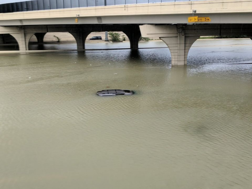 The roof of a submerged car is just barely visible beneath a bridge in Houston on
