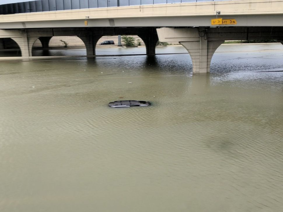 The roof of a submerged car is just barely visible beneath a bridge in Houston on Sunday.
