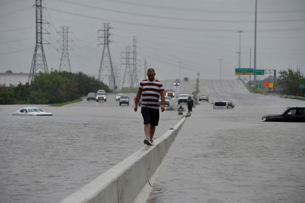 A stranded motorist escapes floodwaters on Interstate 225 in Houston on Sunday.
