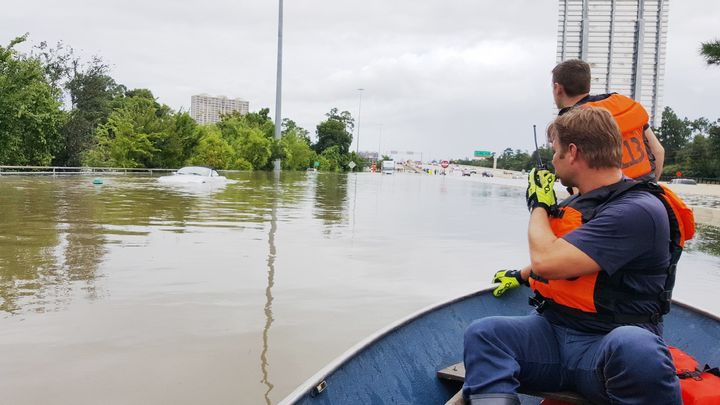 Firefighters with the Houston Fire Department check on a submerged vehicle off Interstate 10 in Houston on Sunday.