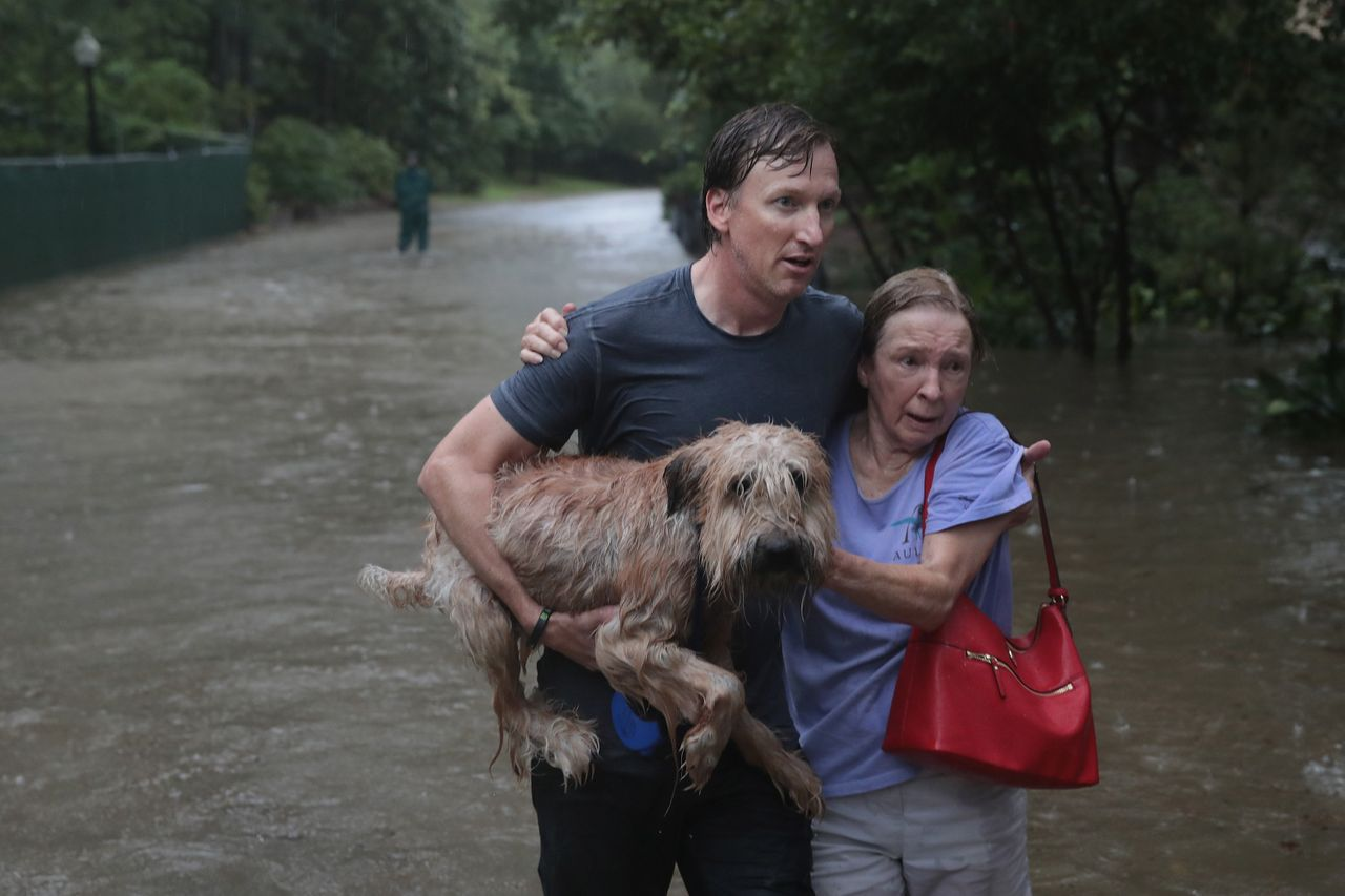Andrew White (left) helps a neighbor down a street after rescuing her in his boat in Houston's River Oaks neighborhood.