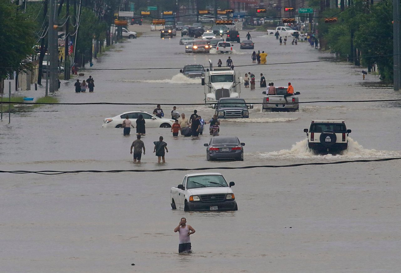 People walk through the flooded waters of Houston on Sunday.