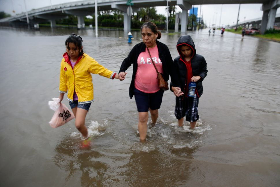 Ofelia Castro leads her grandchildren across a flooded street as they continue an hours long trek from their flooded house in