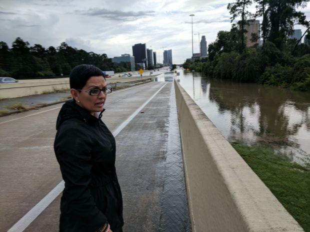 Rosanna Moreno looks over the flooded Buffalo Bayou on Interstate