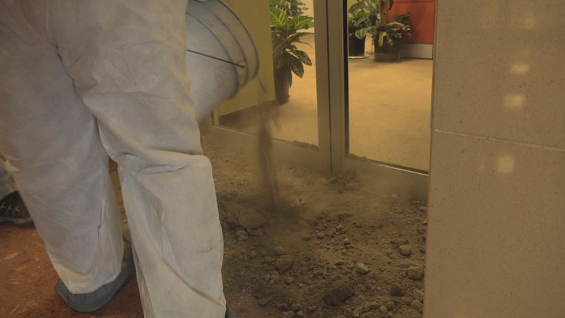 An unknown activist pours coal ashes inside a local government building where the Board of Environmental Quality (JCA) and th