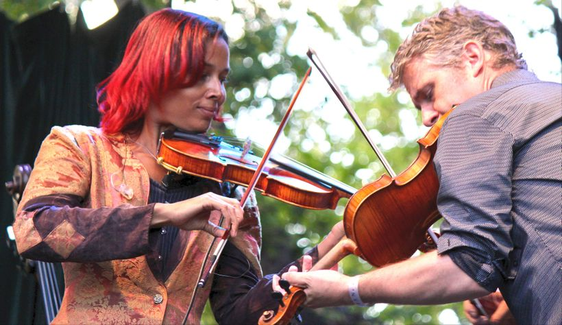 Rhiannon Giddens (left) and <em>Freedom Highway</em> co-producer and cowriter Dirk Powell play the fiddle on Aug. 18 at the 2