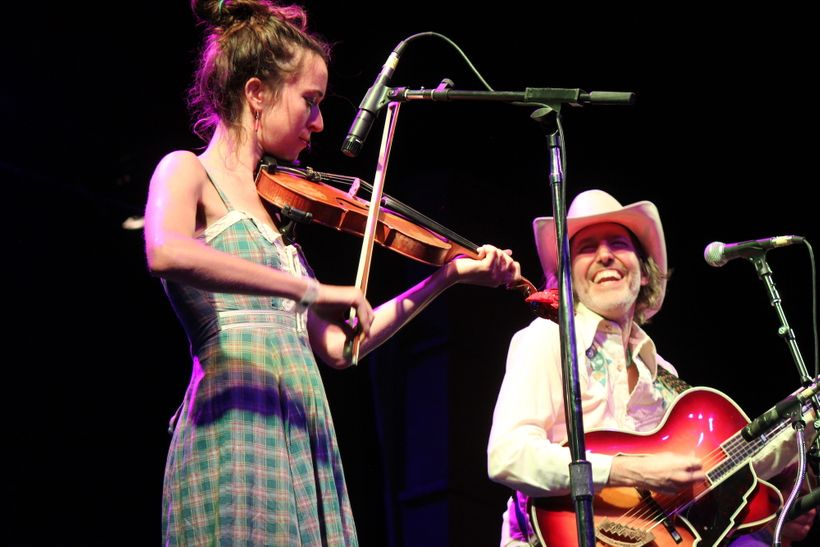 Dave Rawlings (right) enjoys a moment onstage with fiddler Brittany Haas on Aug. 20 at the Folks Festival.