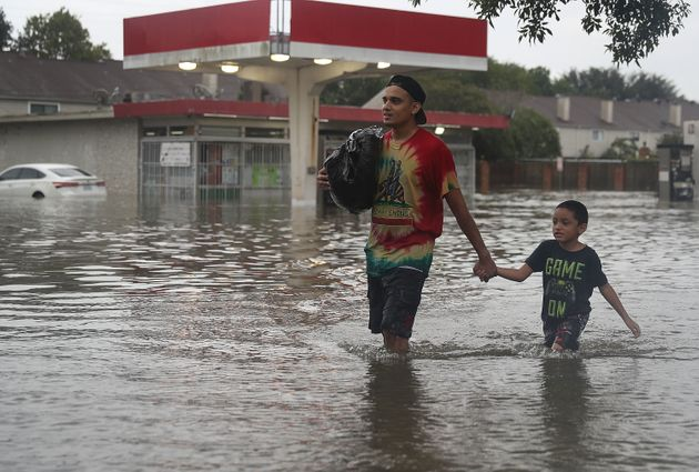 People walk down a flooded Houston street as they evacuate their homes Sunday after Hurricane Harvey