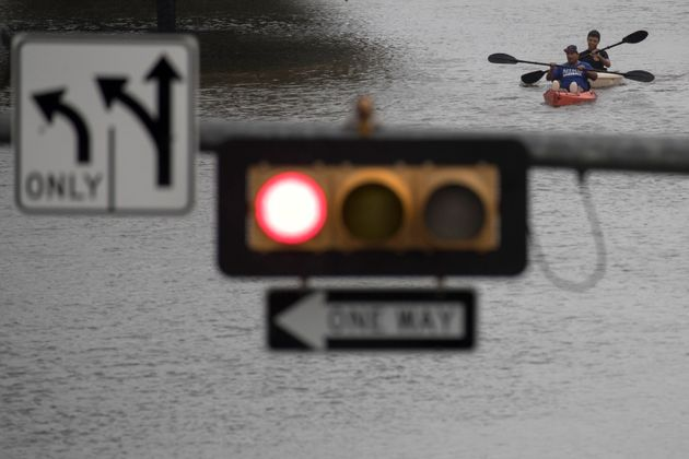 Men use kayaks to get through an intersection after heavy rain from Hurricane Harvey flooded Pearland,...