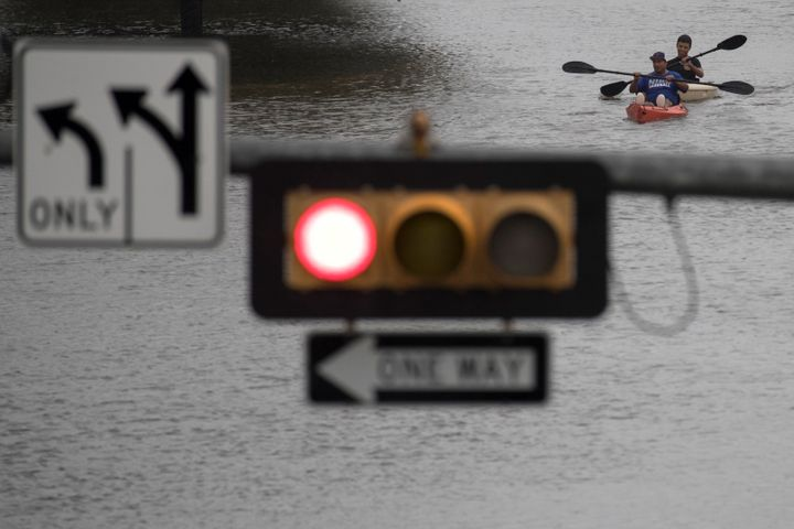 Men use kayaks to get through an intersection after heavy rain from Hurricane Harvey flooded Pearland, in the outskirts of Ho