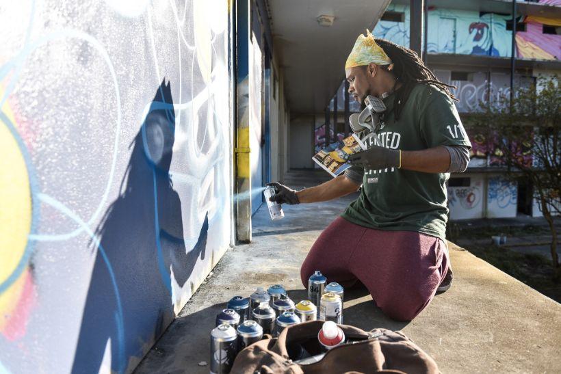 """Brandan Odums spray-paintsa wall for """"Exhibit Be"""" in 2014."""