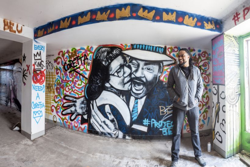 Brandan Odums in front of a portrait of Coretta Scott King and Martin Luther King Jr. in his