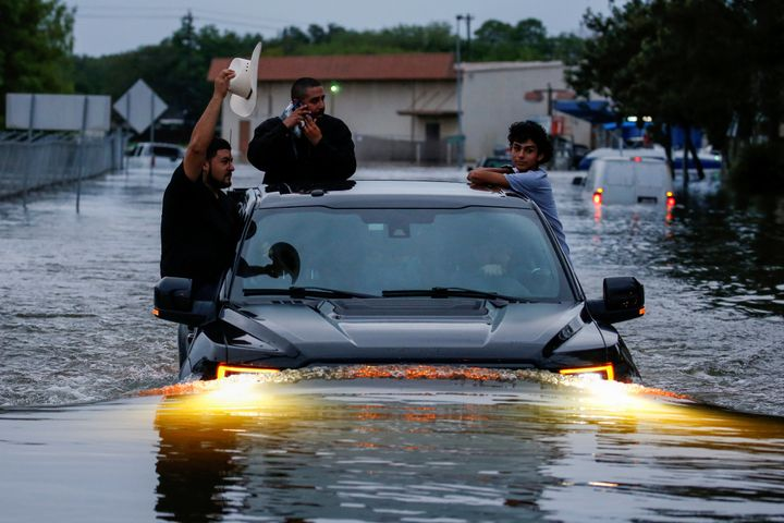 Residents use a truck to navigate through flood waters from Tropical Storm Harvey in Houston on Aug. 27.