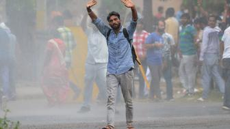 A supporter of Indian religious leader Gurmeet Ram Rahim Singh gestures towards security forces during clashes in Panchkula on August 25, 2017. At least 14 people were killed and dozens more wounded August 25 when violent protests erupted over a court's decision to convict a controversial Indian guru for raping two devotees, a local hospital official said.  / AFP PHOTO / MONEY SHARMA        (Photo credit should read MONEY SHARMA/AFP/Getty Images)