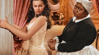 Vivien Leigh (1913-1967), British actress, has her corset tightened by Hattie McDaniel (1892–1952), US actress, in a publicity still issued for the film, 'Gone with the Wind', 1939. The drama, directed by Victor Fleming (1889-1949), starred Leigh as 'Scarlett O'Hara', and McDaniel as 'Mammy'. (Photo by Silver Screen Collection/Getty Images)