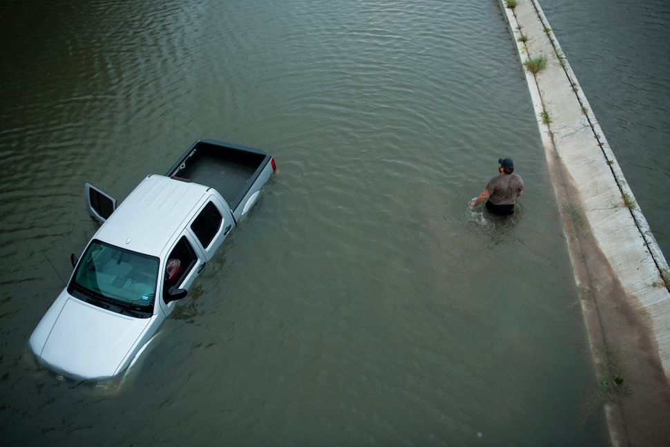 A truck driver walks past an abandoned truck while checking the depth of an underpass in Houston.