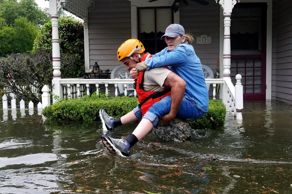 In this handout provided by the Army National Guard, a Texas National Guardsman carries a resident from her flooded home