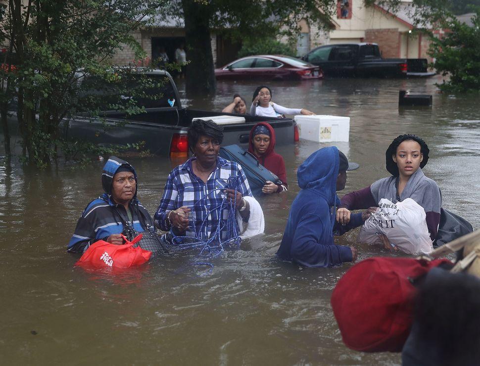People walk down a flooded street in Houston.