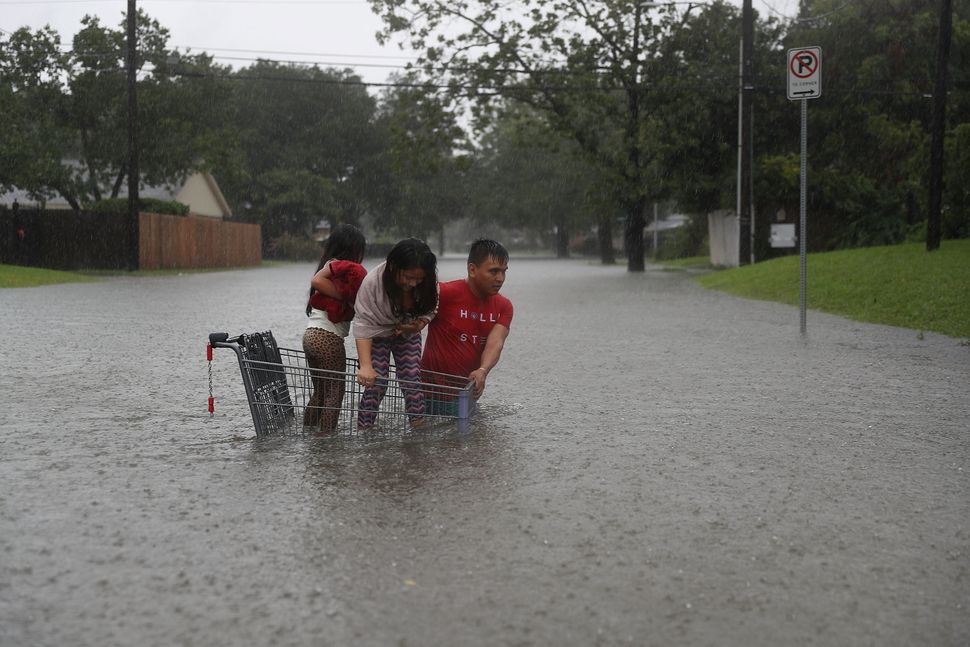 A man helps children across a flooded street in Houston.