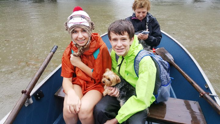 Bobbie, Gracie and Nolen Shumaker boated to safety Monday with their dog Coco in tow.