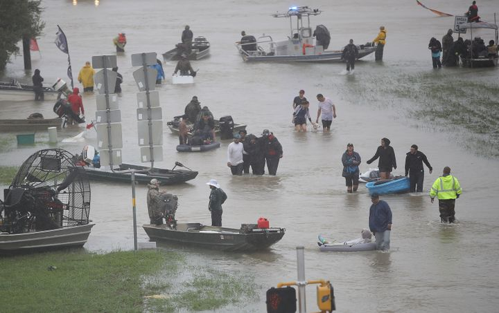Evacuees wade through a flooded street in Houston on Monday.