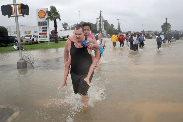 People make their way out of a flooded neighborhood after it was inundated with rain water, remnants...