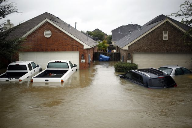 Houses and vehicles at the Highland Glen subdivision stand in floodwaters due to Hurricane Harvey in...