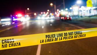 View of a real police crime scene.  Selective focus on the bilingual police cordon tape.