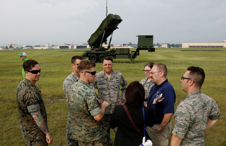 U.S. Forces officials are seen in front of a Japan Self-Defense Forces (JSDF) Patriot Advanced Capability-3 (PAC-3) missile u