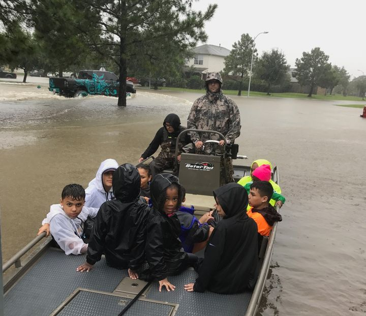 "Joe Spell, a volunteer with the ""Cajun Navy,"" ferries children to safety in Houston on Monday."