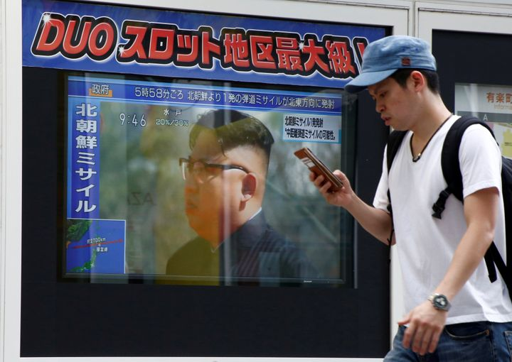 A man walks past a TV set showing North Korea's leader Kim Jong-Un in a news report about North Korea's missile launch in Tok