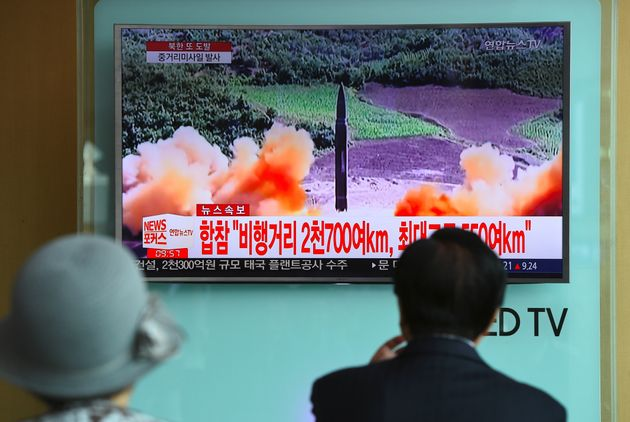 <strong>People watch a television news screen showing file footage of a North Korean missile launch,...
