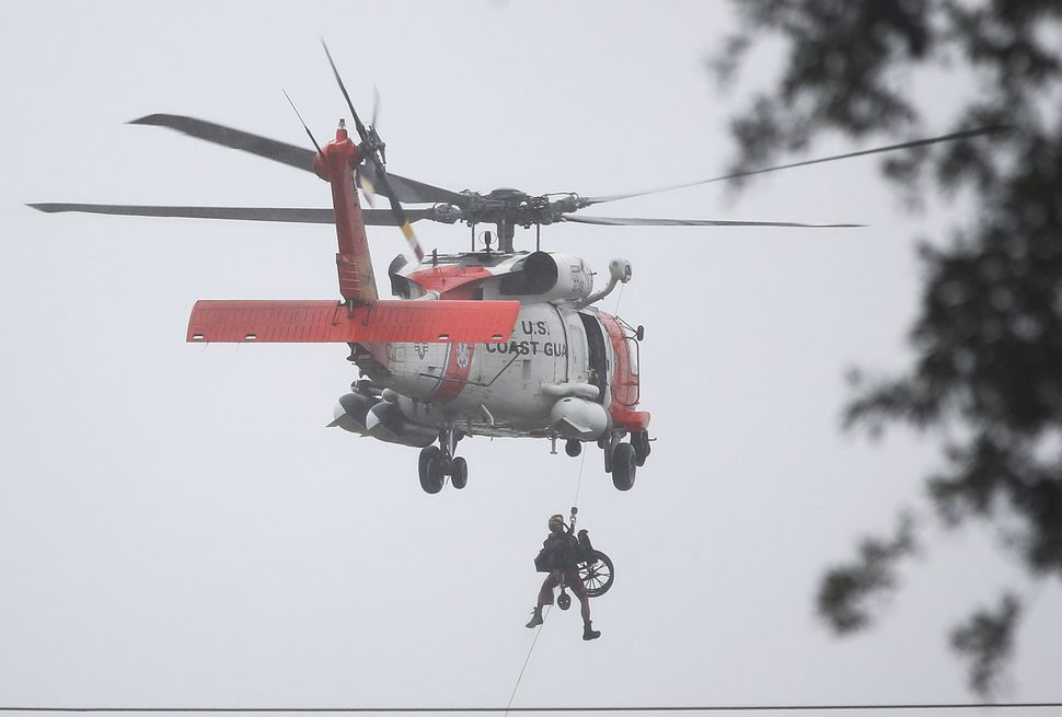 A Coast Guard helicopter hoists a wheelchair onboard after lifting a person to safety in Houston.