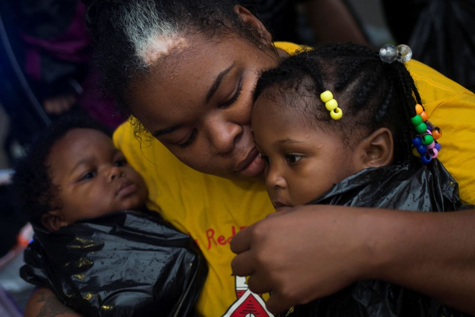 Laquanta Edwards holds her 1-year-old daughter Ladaja, right, and 9-month-old son LaDarius after they arrived to high ground