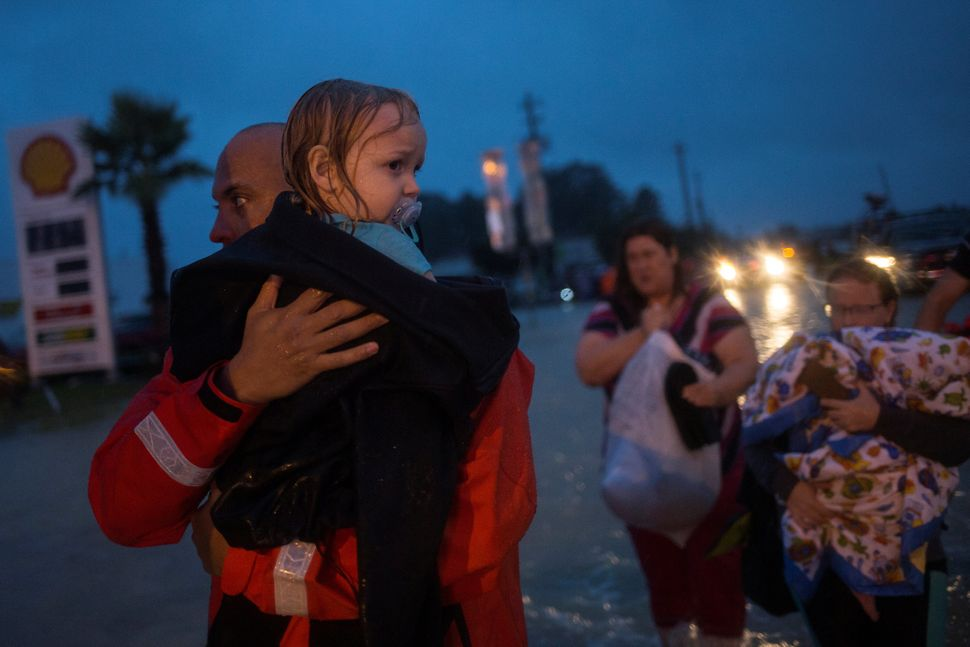 A policeman carries a young girl as her family follows after they fled their home in east Houston.
