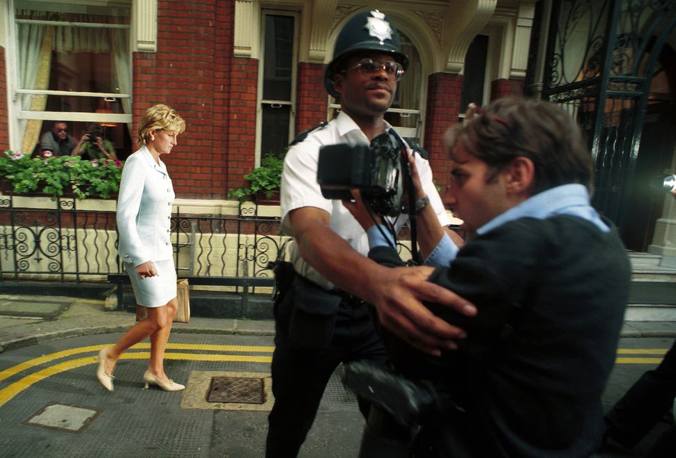 Princess Diana, on the day of her divorce from the Prince of Wales was announced, with a policeman holding back a photographe