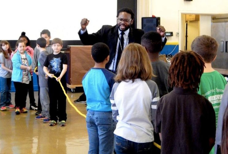 """Charles Woods leads a class in an interactive """"tug-of-war"""" game aroundthe civil rights movement"""