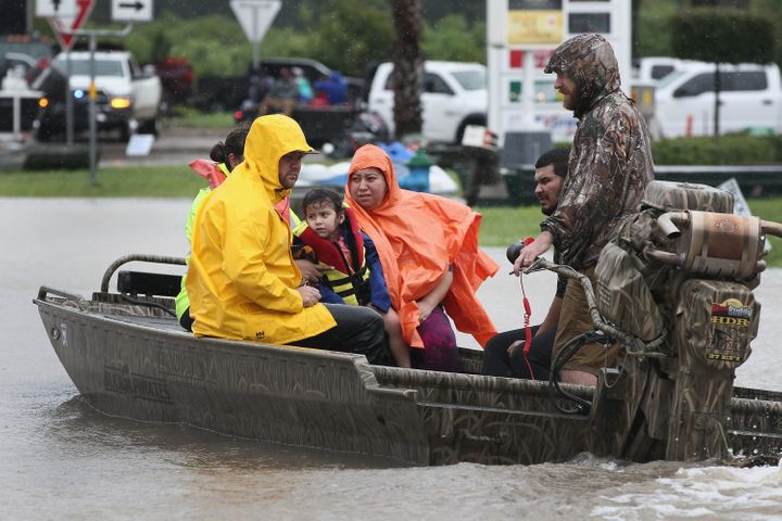 Rescue workers and volunteers help residents make their way out of a flooded neighborhood after it was inundated with rain wa